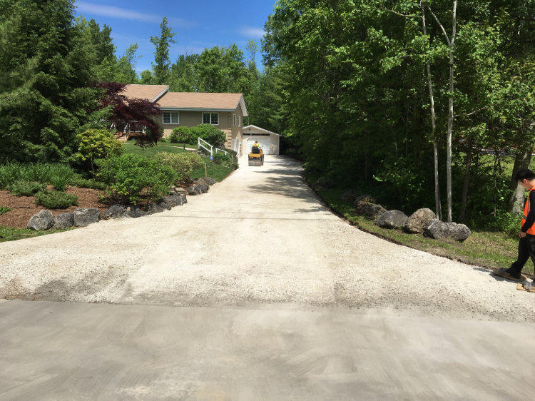 prepping a residential driveway with gravel before paving with asphalt