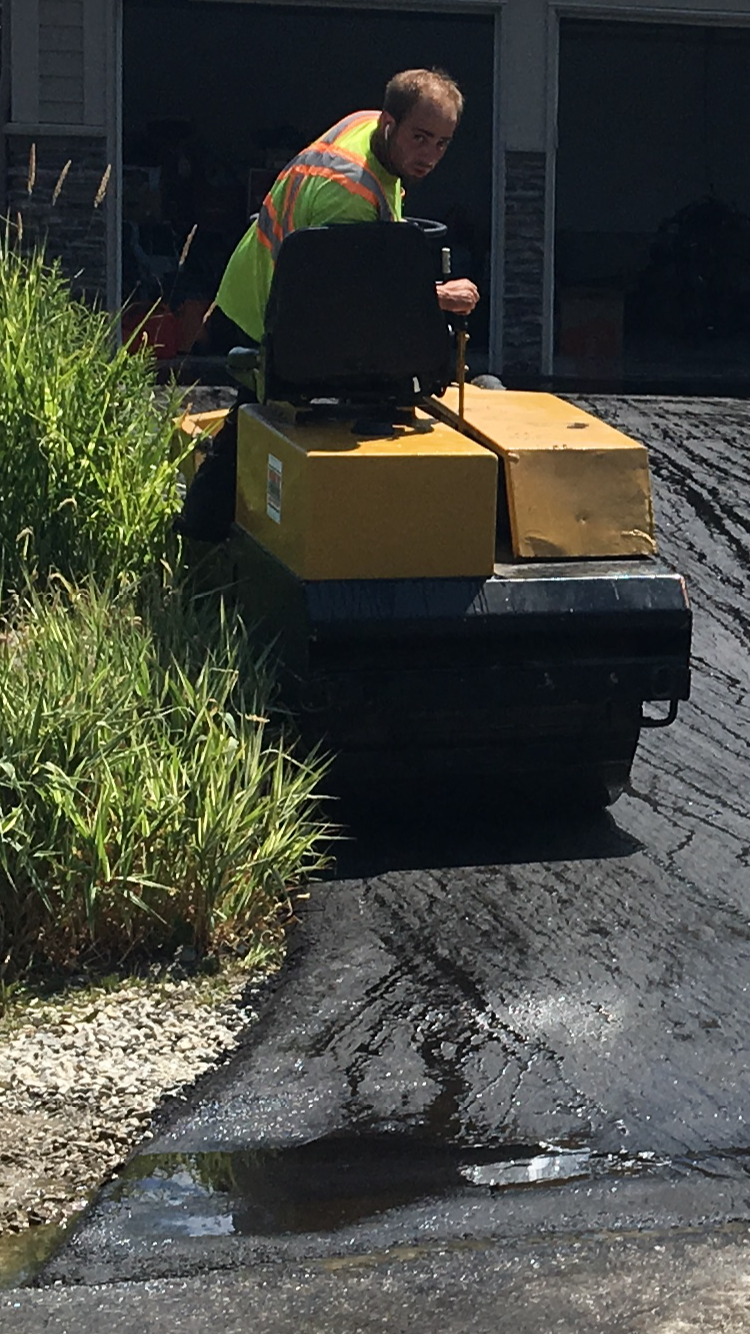 smoothing out the asphalt on a residential driveway
