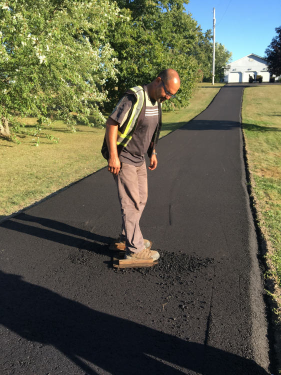 smoothing out the asphalt on a driveway