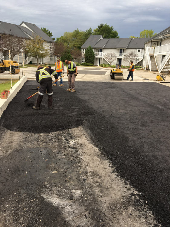 spreading out the asphalt on a residential driveway