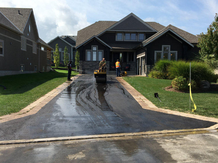 smoothing out the asphalt of a residential driveway