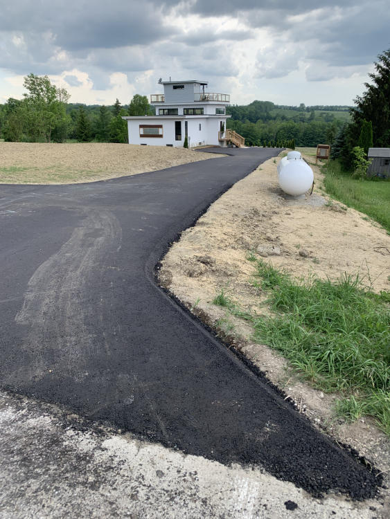 finishing up a new residential asphalt driveway